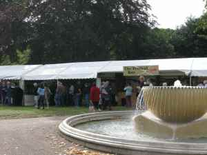 Find us near the fountain - to the left of the festival bar